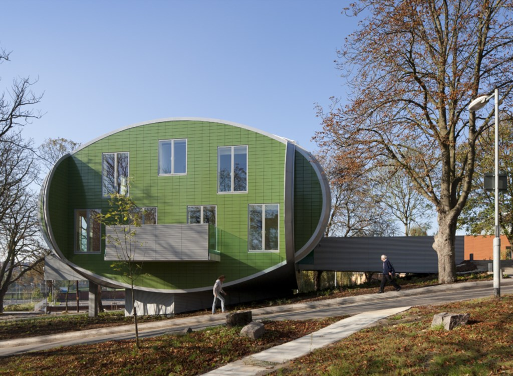 Green oval shaped building with floor to ceiling glazing