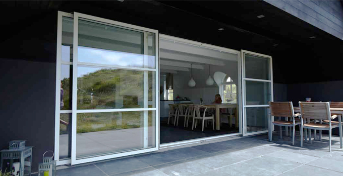 Bi-parting sliding doors in white aluminium frame gives easy acces to air