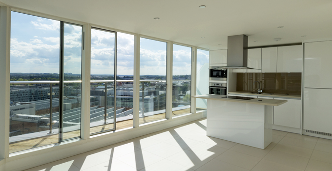 Bespoke floor to ceiling windows combined with a sliding door in a white powder coated finish to the wood frame
